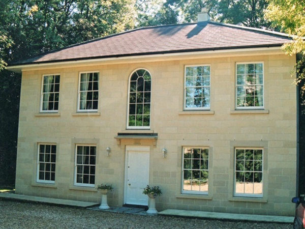 A new two-storey house in Queen Anne style with traditional sash windows in Bath stone.